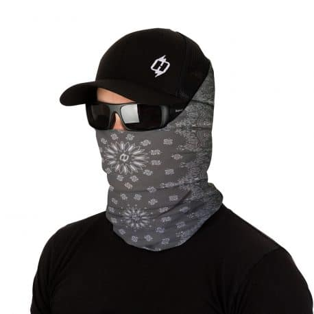 image of a male model in a hat, sunglasses and wearing a paisley patterned bandana on a gray fabric