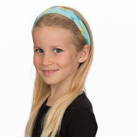 A young girl in a headband of light teal fabric with yellow and teal pineapples