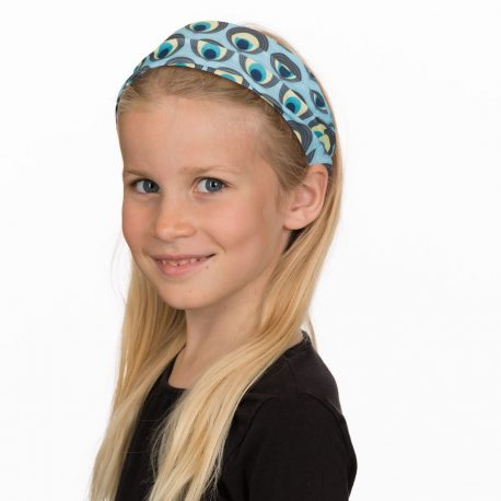 A young girl wearing a headband of light blue fabric with ovals designed to look like peacock feathers