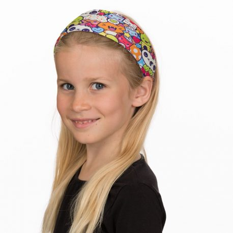 A young girl wearing a headband with a repeating pattern of cartoon pandas, turtles, cupcakes, cats and mushrooms