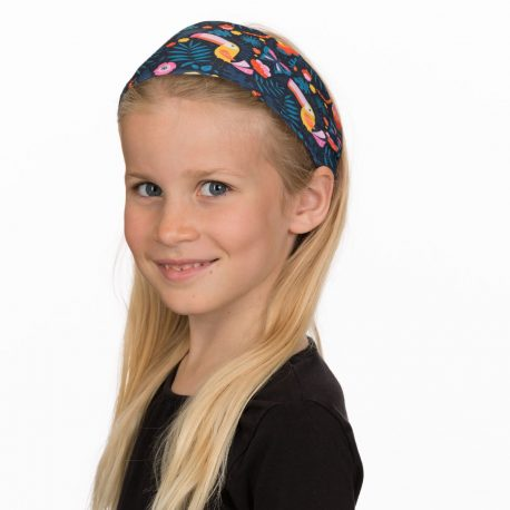 A young girl wearing a navy headband filled with images of sloths, toucans, butterflies and flowers
