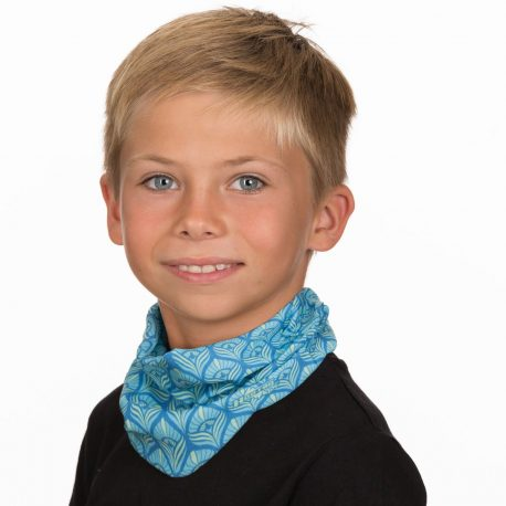 A young boy wearing a neck gaiter of teal and blue oval shapes that resemble peacock feathers