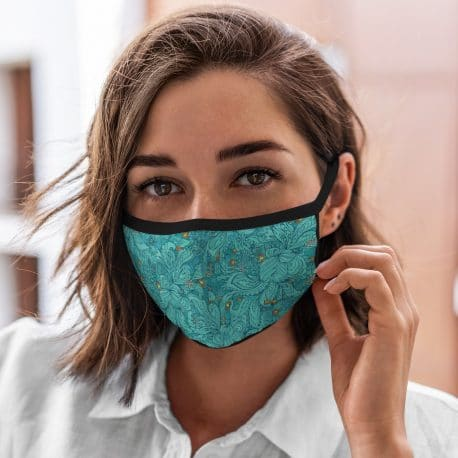 model wearing an ear loop face mask in teal swirls and orange accents with black trim