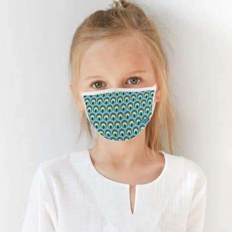 child model wearing an ear loop face mask with teal, green and yellow peacock eyes
