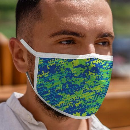model wearing an ear loop face mask with a digital camo design in blue, yellow and green colors