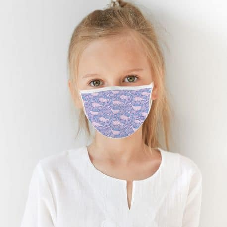 child model wearing an ear loop face mask with pink whales in purple and blue waves