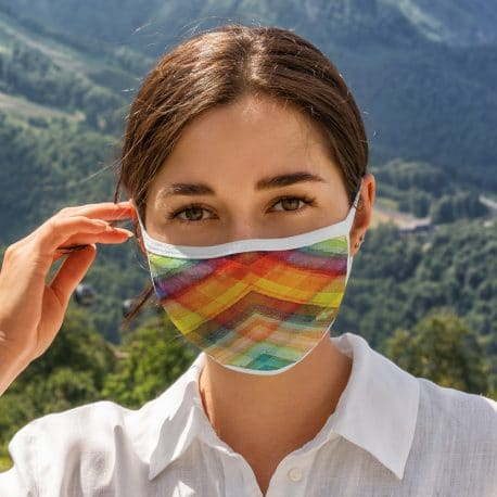 model wearing of an ear loop face mask in multi color overlapping lines with white trim