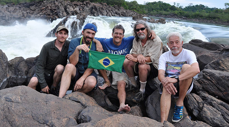Members of the U.S. Expedition team holding the Brazilian Flag Hoo at the downstream most waterfall on the rio Xingu, Brazil.